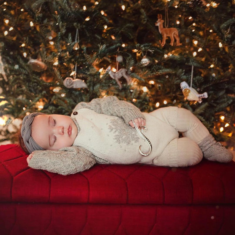 baby under the christmas tree in our hand knitted white snowflake romper