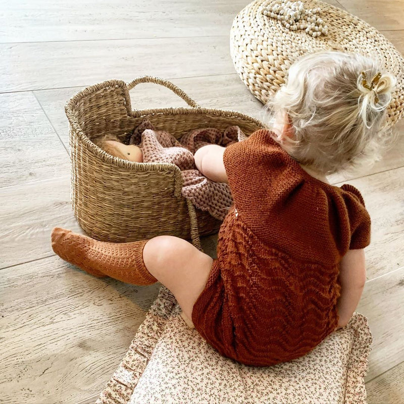 baby girl wearing hand knitted dress on rust