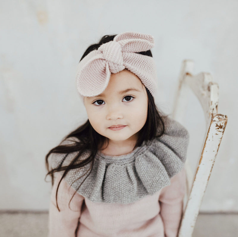 Baby girl wearing hand knitted hairband in dusty pink