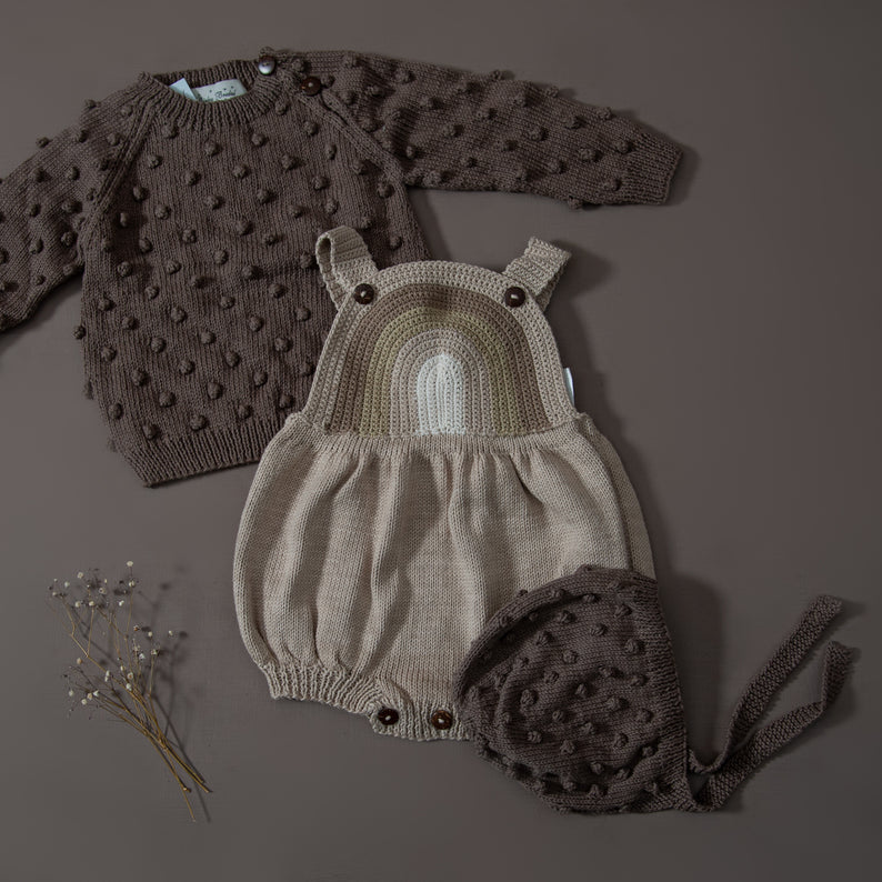 flat lay picture of hand knitted rainbow romper oats along with hand knitted bubble sweater and hand knitted bubble bonnet in nutty brown