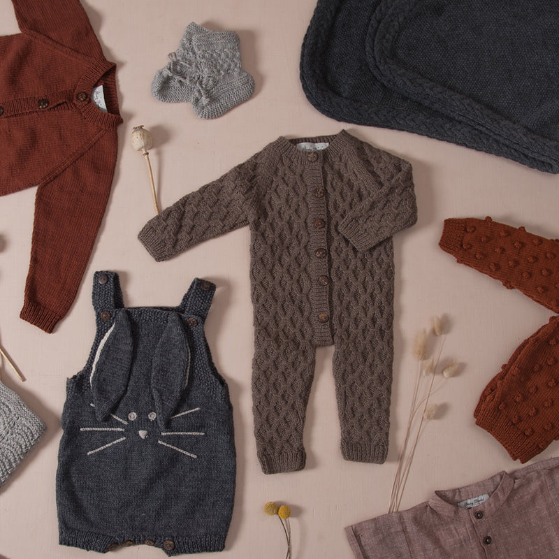 flatlay picture of hand knitted smock playsuit nutty brown along with other baby outfits