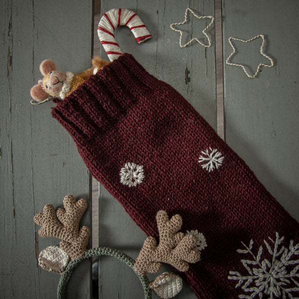 red christmas embroidered stocking filled with gifts