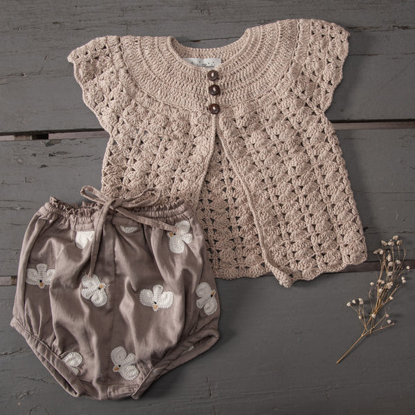 flat lay picture of baby bloomers taupe with bird badge and bella cardigan oats