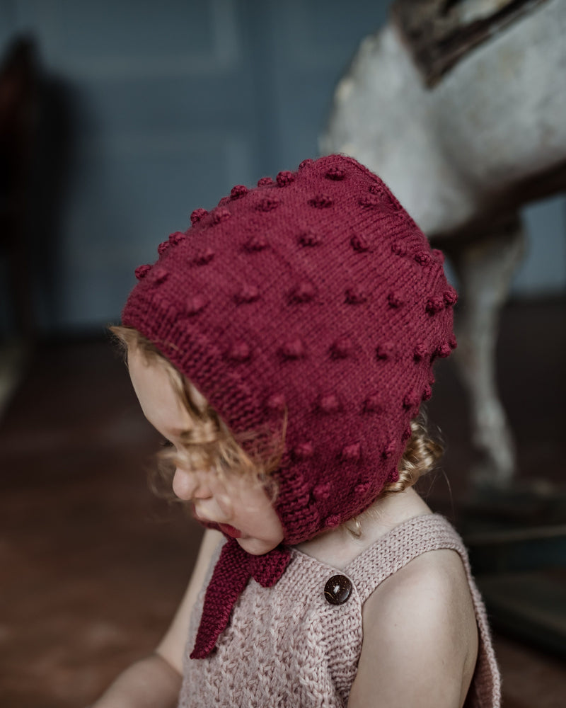 baby girl wearing hand  knitted  bonnet iwith string ties in deep berry color