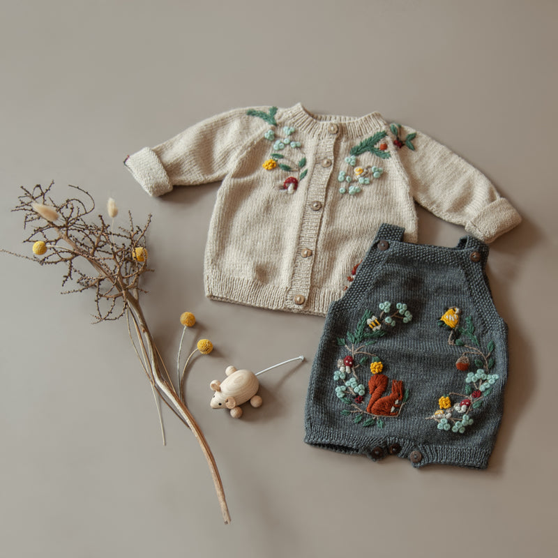 flat lay picture of woodland cardigan oats and woodland  romper dark grey