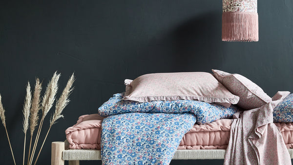 Liberty fabric bedding stack by Coco & Wolf against dark wall.
