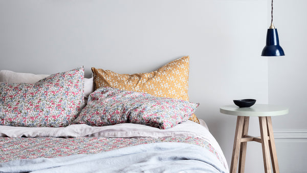Bed made with Liberty fabric bedding by Coco & Wolf using contrasting shades, mustard and pink.