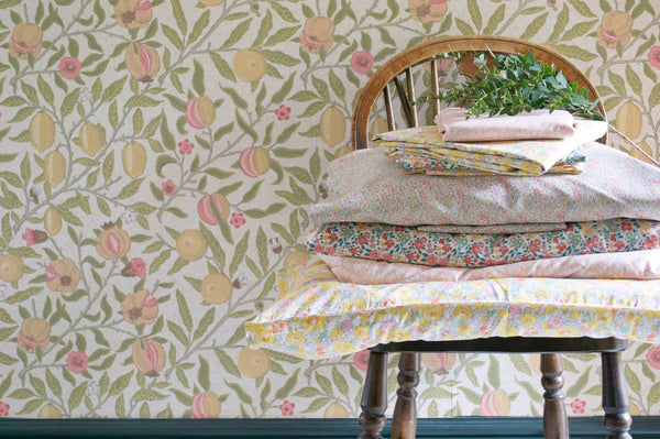 Stack of Liberty print products on a chair against William Morris wallpaper. Spring refresh for your home.