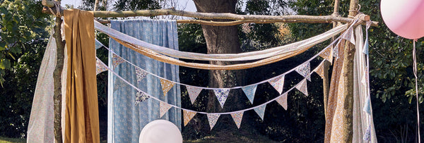 Picnic setting made with Liberty fabric blanket, cushions and bunting.