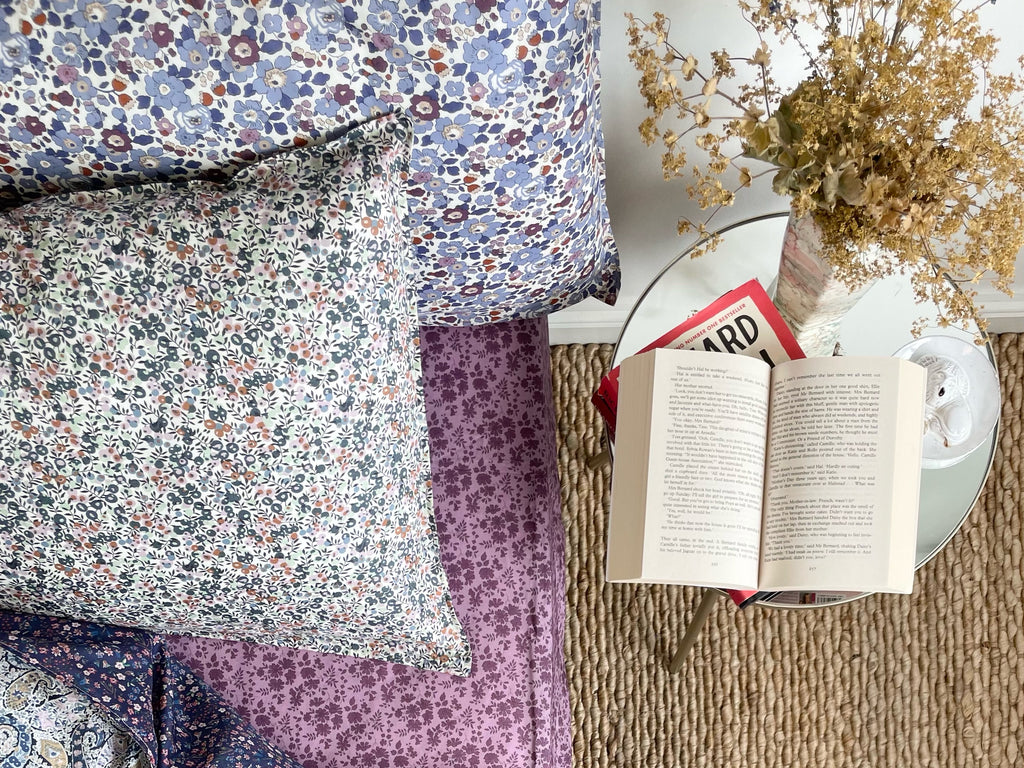Books beside a bed dressed in Liberty fabric bedding by Coco & Wolf