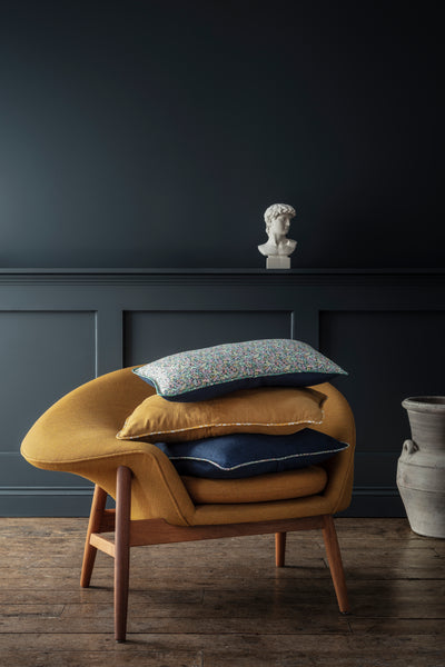 Armchair stacked with Liberty fabric cushions by Coco & Wolf.