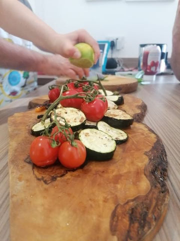 Close up tomatoes and chopped vegetables on a chopping board