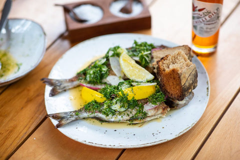 Plate of roast fish with lemon, greens, and bread