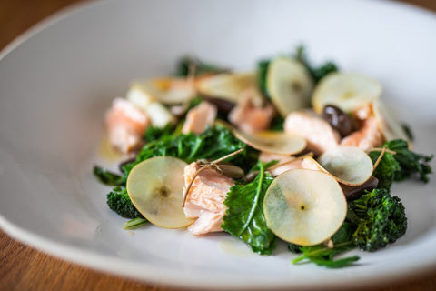 Bowl of green salad with cooked salmon