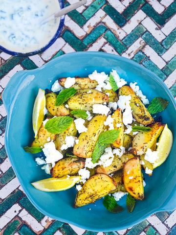 Plate of potato wedges with feta cheese and mint leaves