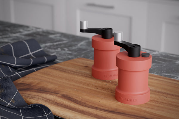 Salt & Pepper Mills Displayed on A Chopping Board With A Marble Worktop - In Coral Red