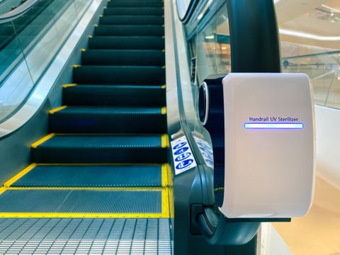 UV light device is attached to an escalator handrail at a shopping mall to disinfect, sanitize, and sterilize the surface from germs, pathogen, viruses, and bacteria