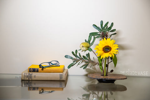 vase on desk with sunflowers and study books