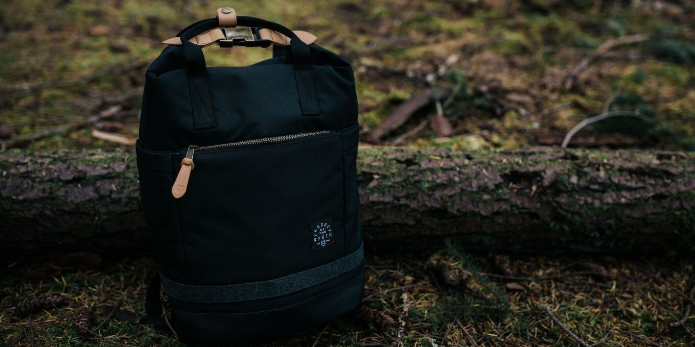 Black Avalon Diaper Bag Backpack propped up against a tree in the wilderness