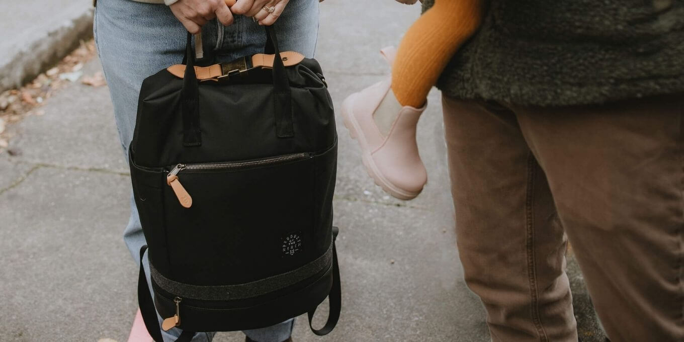 Black Avalon Diaper Bag Backpack being held by woman as a tote standing next to partner and toddler