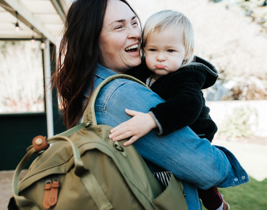 Brunette mom with a blonde baby carrying a Product of the North Sustainable Olive green diaper Diaper bag.