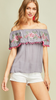 Grey Off-shoulder top featuring embroidery and pom-pom details