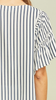 Pinstripe peasant top featuring embroidery details. Self-tie tassel closure at neckline