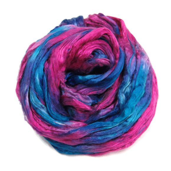 Mulberry Silk varigated roving, hand dyed in tones of Rose and Royal blue.  Color: Theater