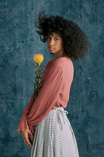 Grapefruit pink fine rib organic cotton sustainable viscose knit top with gathered tie frill cuffs with Gingham pleated & tie skirt with single stem flower