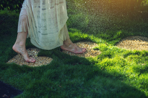 a barefoot woman in a long ivory dress walks on bare earth in green grass