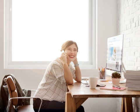 Woman sitting at desk in a bright room and smilinig