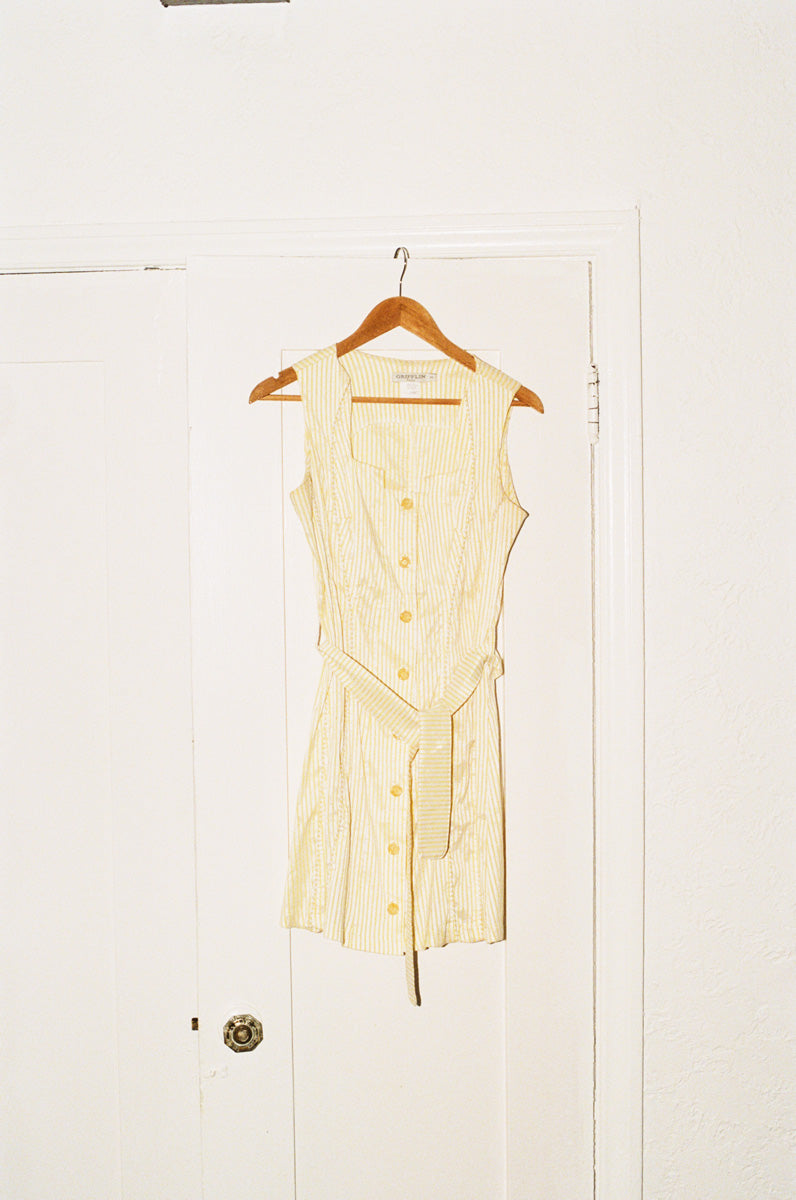 Pale yellow mini dress hanging on a door