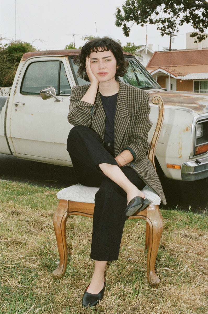 Madelynn sitting on regency style chair on a front lawn next to a car