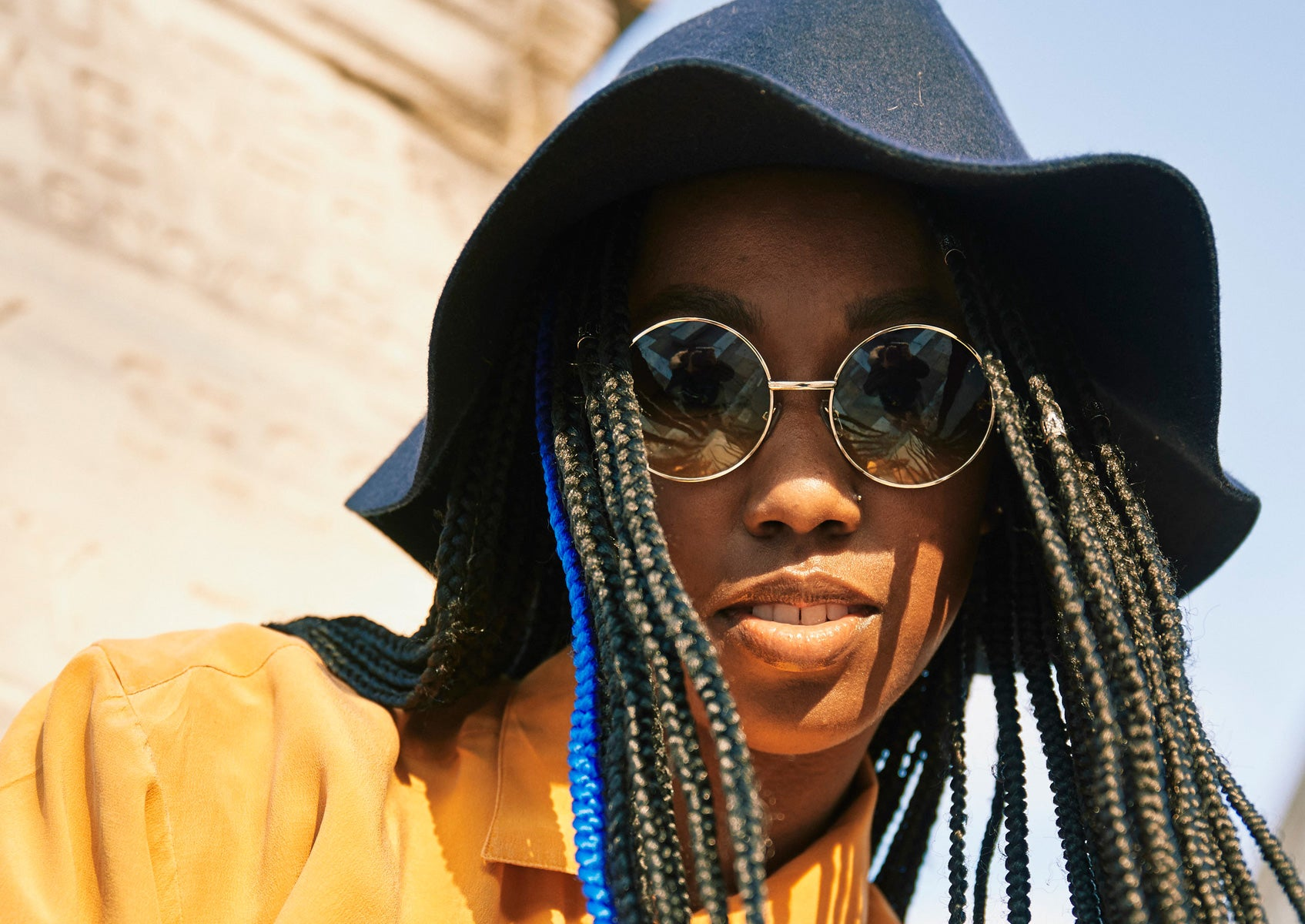 Dominique Drakeford wearing a bucket hat and sunglasses