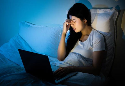 A woman on her computer in bed.