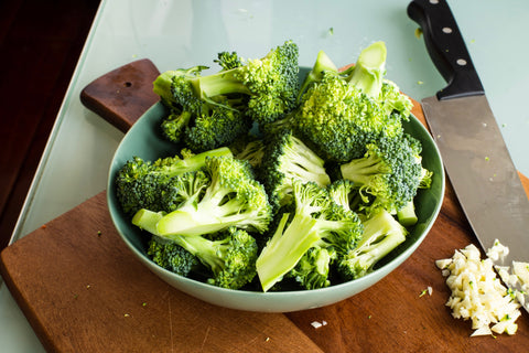 Broccoli in a bowl with a knife.