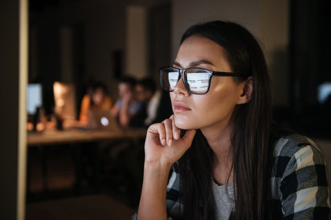 A girl with glasses on her computer.