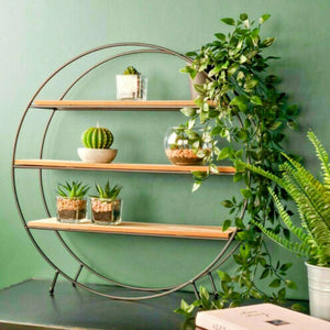 circular metal and wooden shelves holding various artificial plants and accessories with artificial vines on side