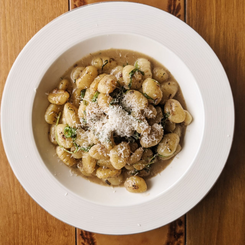 Bowl of gnocchi topped with grated parmigiano cheese on a walnut table top