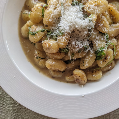 Bowl of Gnocchi in a Butter Emulsion Topped With Grated Parmigiano Reggiano Cheese