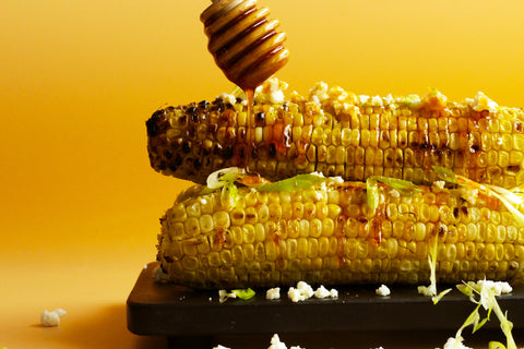 Stacked Corns on Cobs with a Honey Drizzling On and Topped with Feta and Scallions