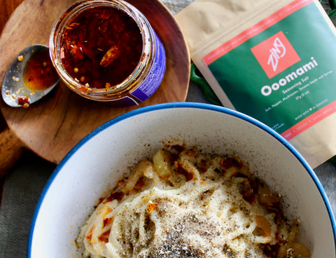 Cauliflower Cheese Pasta in A Bowl With A Package of Ooomami Salt and Open Jar of Hakka-ish Chili Crisp