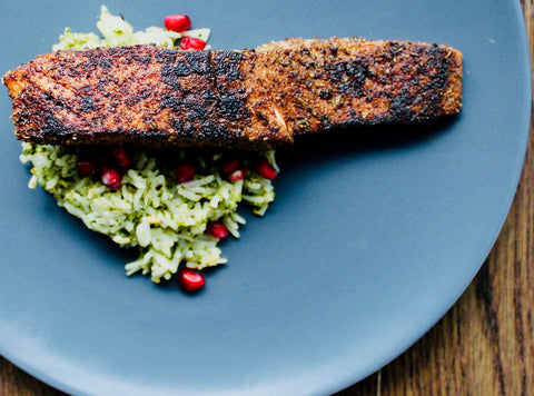 Photo of a pan-seared piece of salmon over herby, pomegranate rice in a blue plate.