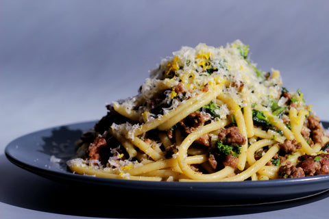 Side view of a blue plate of bucatini with specs of rapini and lamb and topped with grated parm