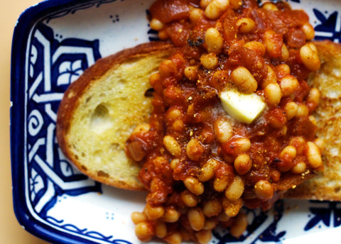A piece of toast on a blue and white plate loaded with baked beans and a blob of butter