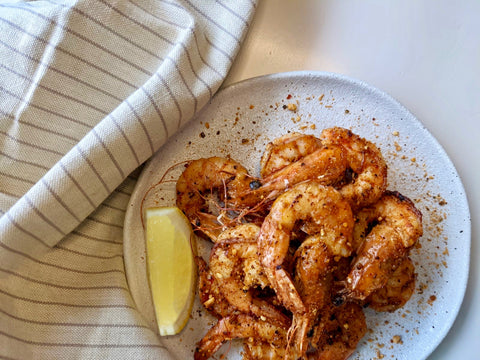 White plate with golden-brown pan fried shrimp using Zing Boom Seasoning Salt and lemon wedge
