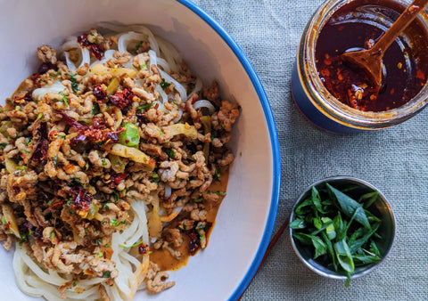 A bowl of Dan Dan Noodles next to an open jar of Hakka-ish Crisp and a small plate of scallions