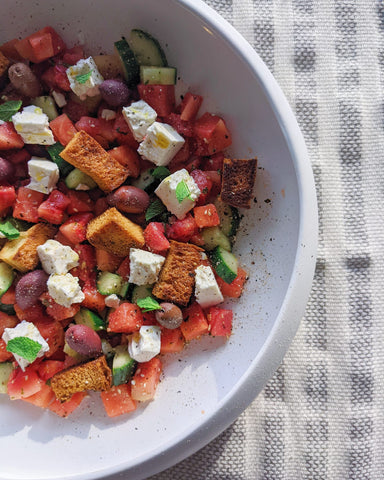 Three quarters of a large white bowl of a salad of croutons, cucumber, watermelon, and chunky squares of feta sprinkled with ooomami seasoning salt. Backdrop is a grey and white striped linen, slightly crushed. Photo taken in natural light