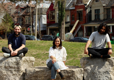 The three Zing founders - Kiran, Jannine, and Anush - sitting socially distant in a park un Toronto with a row of houses in the background