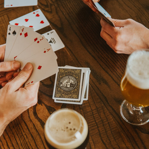 Two sets of hands holding playing cards.